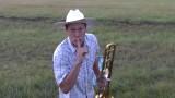 Allevatore si siede in mezzo al campo e inizia a suonare il trombone, perchè lo fa?