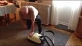 Uomo di casa che cerca di mettere in moto l'aspirapolvere